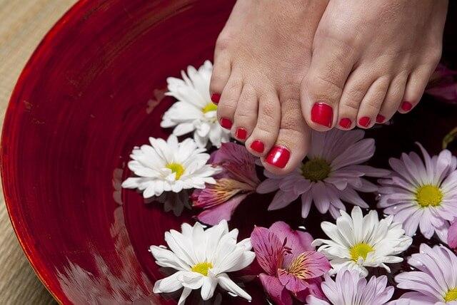 Stopy kobiety nad misą z kwiatami