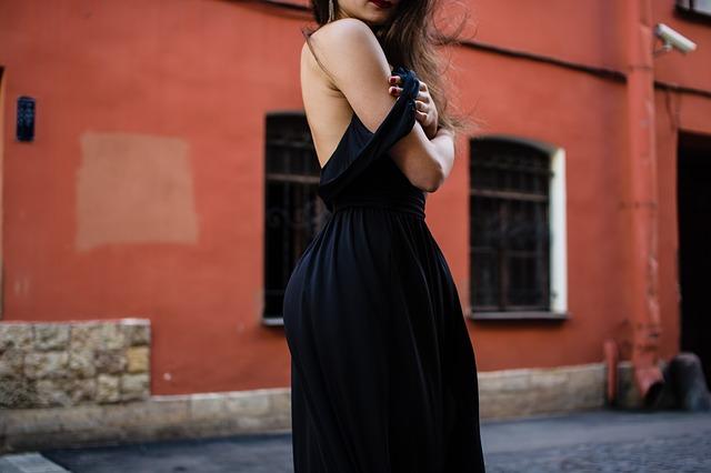 Dziewczyna w ciemnej sukni odsłaniającej ramię