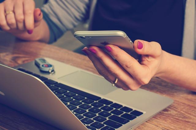 Kobieta siedzi przed laptopem i trzyma smartfon