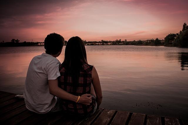 Para siedzi nad wodą o zachodzie słońca